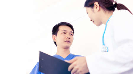 two asian doctors discussing in hospital, male and female physicians wearing medical uniform, concept of specialist teamwork Standard-Bild