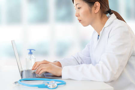 concentrated asian female doctor typing on laptop in clinic office, hospital physician lifestyle