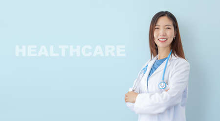 beautiful asian female doctor smiling, portrait of woman physician isolated on blue background
