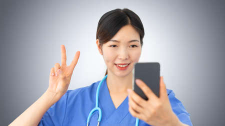 beautiful asian female doctor takes a selfie gesturing the victory sign with her fingers, confident health care professional makes a positive sign while holds a mobile