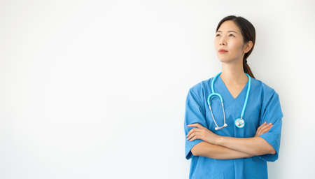 asian female doctor in blue uniform with crossed arms looks upwards pensive, young medical practitioner isolated on white background