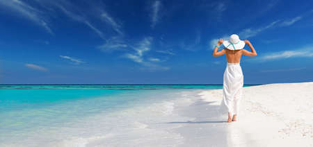 elegant woman in white dress holds sun hat and walks on idyllic beach of maldives, relax in a tropical island