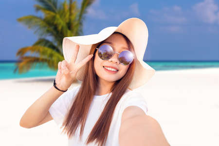 young woman with a floppy sun hat and sunglasses takes a selfie in a tropical paradise, vacation memories of a cheerful girl
