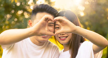 happy young asian couple make heart sign with hands in a sunny day at the park