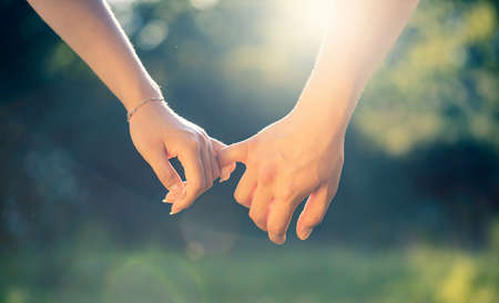young couple holding hands at sunset, close-up detail of pinkies in sunlight, love and romance gesture or symbol