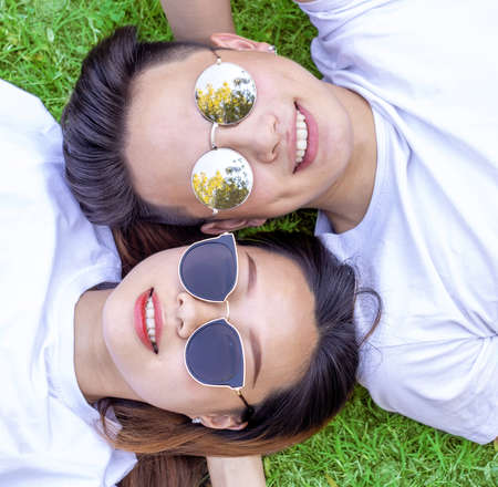 young boy and girl with sunglasses lying down on grass and smiling, overhead view of a cheerful asian couple resting on a meadow Standard-Bild
