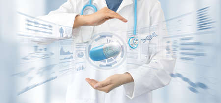female doctor in white coat and stethoscope protects with the hands a capsule in a stats data background, pharmaceutical research and health cure safety