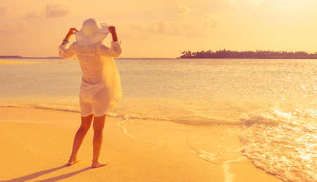 stylish girl watches the sunset on a tropical beach of a maldives island with white hat and shirt with her feet in the soft sand
