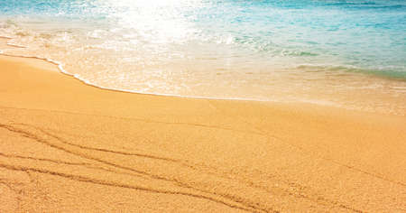 soft sand beach by the sea with crystal clear water of a tropical island. The waves reflect the sunset light