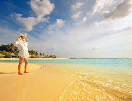 stylish girl watches the sunset on a tropical palm fringed beach of a maldives island with white hat and shirt with feet in soft sand Standard-Bild