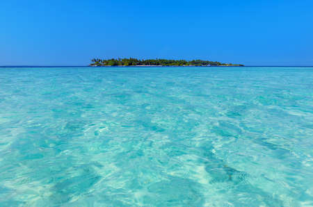 view of a paradise island fringed with coconut palms taken from the sea. The blue and transparent water of the coral reef entice you to an exclusive holiday Standard-Bild