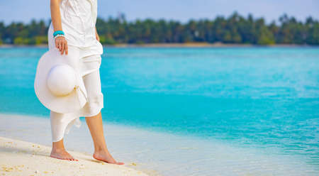 Elegant woman with pareo and hat relaxes walking on the white sand of a beach in the Maldives, bathes her feet in the crystal clear water of the turquoise lagoon sea with a background of coconut palms Standard-Bild