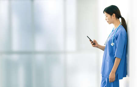 Female doctor texting during a break from work shifts. Concept of stress and fatigue from work in the hospital during the pandemic.
