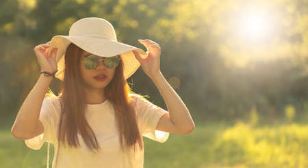 Asian girl walks serene in the park at sunset holding her hat with her hands. Young tourist relaxing
