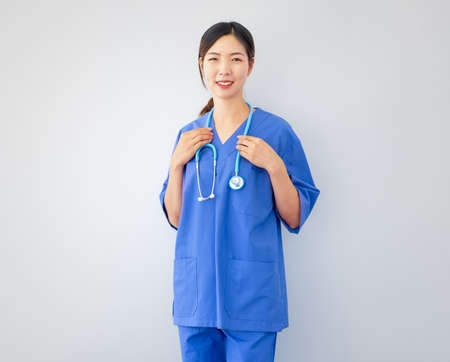 Smiling Asian female doctor wearing blue hospital uniform with stethoscope standing in front of white background