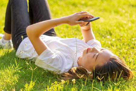 young girl lying on the grass listens to music texting in a park with sunset light