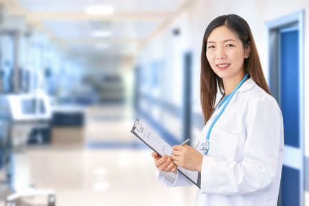 Smiling Asian female doctor wearing lab coat and stethoscope as she writes a document in her folder. In the blurred background you can see the hospital ward with medical equipment and patient rooms Standard-Bild