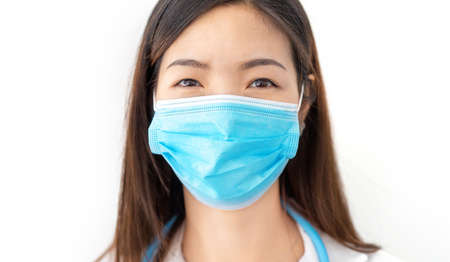 female health worker during the coronavirus pandemic protects herself by covering her face with a mask