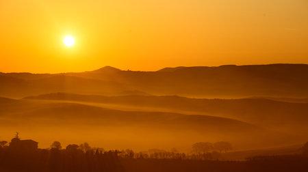 warm dawn sun on misty rolling hills in the tuscany countryside Standard-Bild