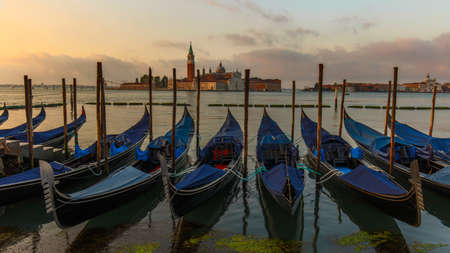 Gondolas moored in St. Mark's Square facing San Giorgio Maggiore church. Dawn in Venice, Italy