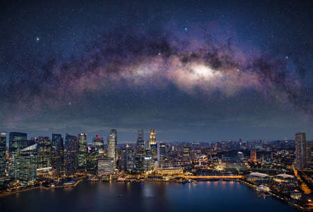 Milky way in Singapore night sky. Illuminated skyscrapers in the central district waterfront. Standard-Bild