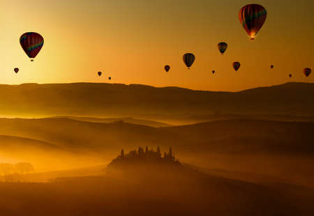 group of hot air balloons flying at dawn above the misty hills in Tuscany