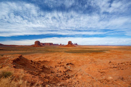 Panoramic view of Monument Valley Navajo Tribal Park landscape. Majestic rock formations under a cloudy blue sky in USA.