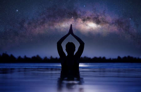Silhouette of a woman practicing yoga lotus pose in infinity swimming pool under a starry sky with milky way arch