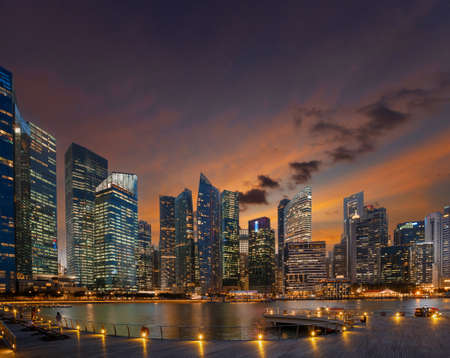 Singapore central business district view from illuminated waterfront promenade at sunset.