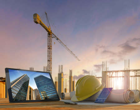 Engineer or architect's tools in construction site at sunset. Tablet, hard hat and blueprints on wooden table with crane and building rebars on the background. Standard-Bild