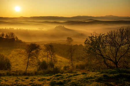 Warm dawn on tuscan countryside. Fall and foggy rural landscape