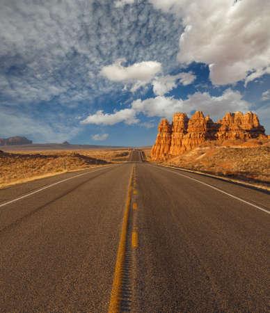 Empty road under a cloudy blue sky in Arizona desert. US southwest scenery.