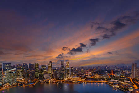 Singapore downtown skyline at sunset. Dramatic twilight sky above financial district waterfront buildings.