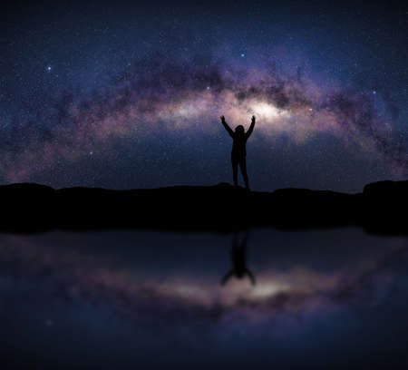 Female silhouette raises arms in front of a bright Milky Way night sky. Concept about open air sport activity, adventure, travel. Standard-Bild