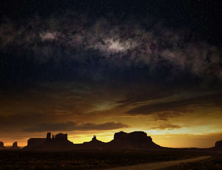 desert landscape in Monument Valley under a starry twilight sky with Milky Way galaxy.