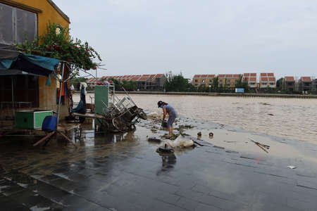 Hoi An, Vietnam, October 13, 2020: A woman cleans the entrance of her home along the Thu Bon River after severe flooding due to a tropical storm.