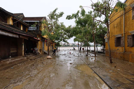 Hoi An, Vietnam, October 13, 2020: Workers clean street's mud after severe flooding due to a tropical storm.