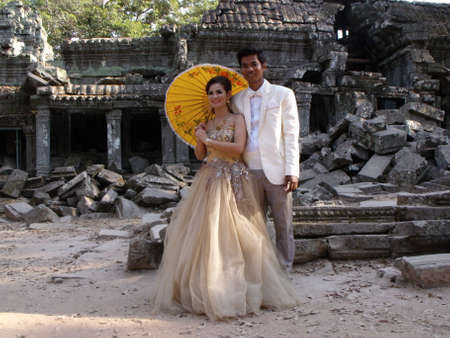 Siem Reap, Cambodia, April 6, 2016: A newly married couple is photographed at the Ta Prohm temple in the Khmer temple complex of Angkor