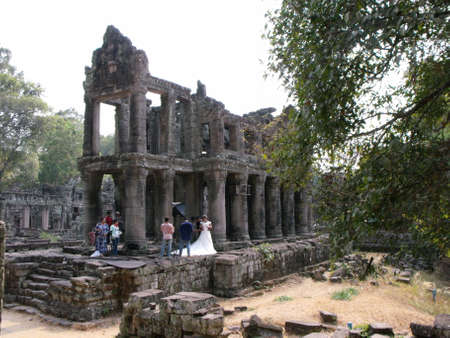 Siem Reap, Cambodia, April 8, 2016: A newly married couple takes photos in one of the temples in the Khmer temple complex of Angkor
