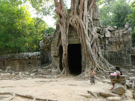 Siem Reap, Cambodia, April 8, 2016: Two children next to a large tree that grows over the stone entrance to a temple in the Khmer temple complex of Angkor 新聞圖片