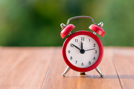 Red vintage clock on natural background. Autumn time change Stock Photo