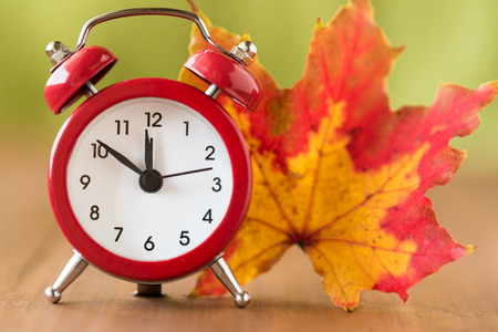 Red vintage clock and mable leaf. Autumn time change Stock Photo