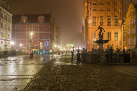 Beautifully illuminated Old Town in Gdansk with fountain of the Neptune. Foggy night. Poland.