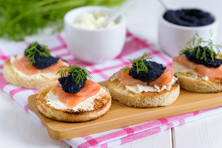 Appetizer toast with cream cheese, smoked salmon and black caviar decorated by dill.