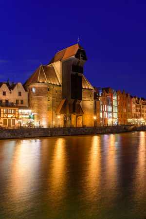 Gdansk at night with famous historic port crane reflected in Motlawa river. Poland, Europe.