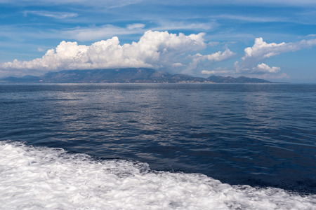 Water trail foaming behind a ferry boat in Ionian sea, Kefalonia island in background. Greece, Europe. Stock Photo