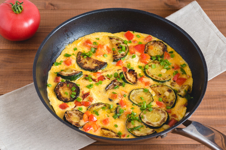 Omelette with zucchini, red paprika and chives. Frittata in frying pan on wooden board.