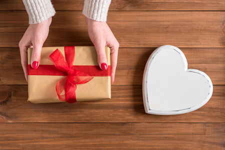 Female hands giving gift on wooden background. Stockfoto
