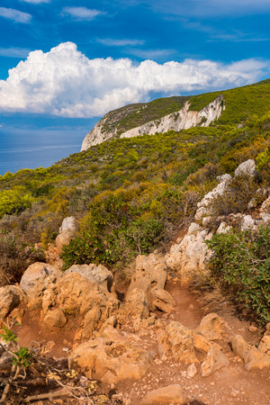 Rocks and dry grass on seaside cliff. Beautiful view of sea waters and coast on Zakynthos island Greece.