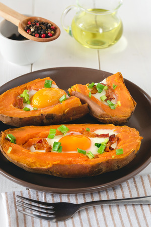 Baked sweet potato with fried egg, bacon and chives.
